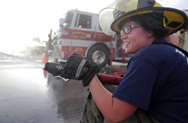 Kimberly firefighter Alexis Metko directs water from a hose during a training exercise. Metko has recovered from fractures to her skull, femur and wrist that she suffered two years ago in a fall from a ladder at Fox Valley Technical College.