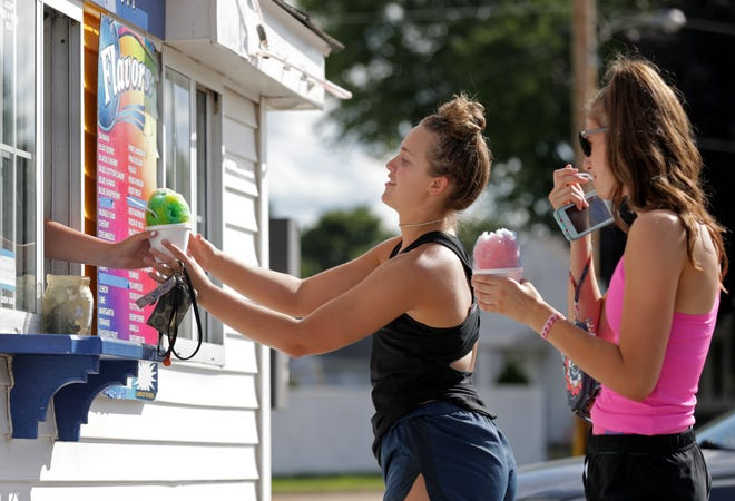 Kiara Schmidt and Maddy Schreiber, right, beat the heat while enjoying a snow cone from Sno-Biz Tuesday in Kimberly. Excessive heat will continue hovering over the Fox Cities through the week.