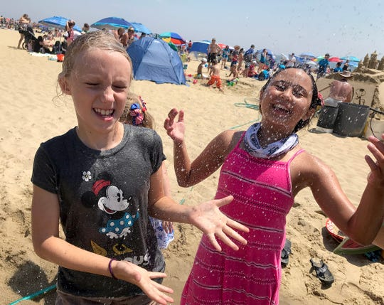 Kaylee Connors (left), Glen Gardner, and Luna Zipkin, 8, Middlesex, cool off under the showers on the Belmar beach Wednesday, July 17, 2019.
