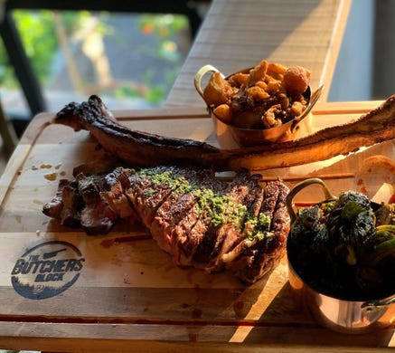 A tomahawk steak and sides at The Butcher's Block in Long Branch.