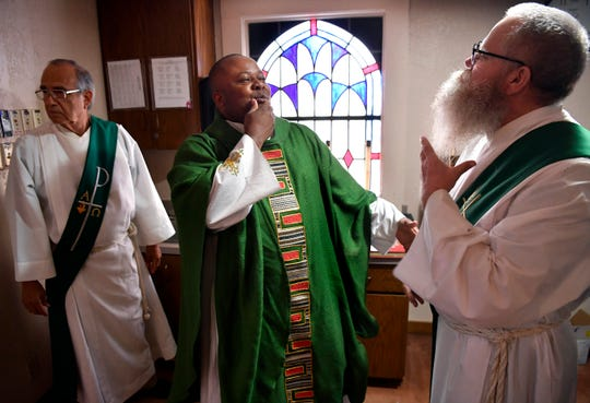 The Rev. Albert Ezeanya (center) and Deacon Dwain Hennessey discuss beard care in the sacristy at Sacred Heart Catholic Church. They and Deacon Art Casarez were awaiting the start of Mass to install Ezeanya as the parish's new priest.