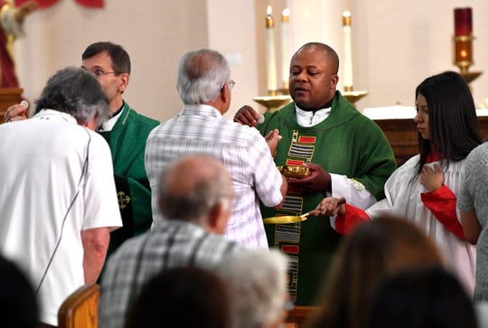 The Rev. Albert Ezeanya Jr. offers communion after being installed as priest at Sacred Heart Catholic Church.