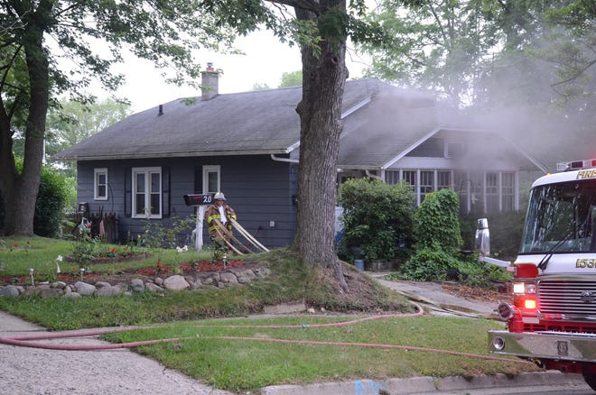 The first firefighters to arrive begin to pull hose to the back of the house at 18 Montford St.