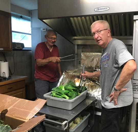 Brothers Don and Paul Kumpon boil cabbage leaves at St. Cyril's Church on July 17, 2019 in preparation for St Cyril's Parish Festival.
