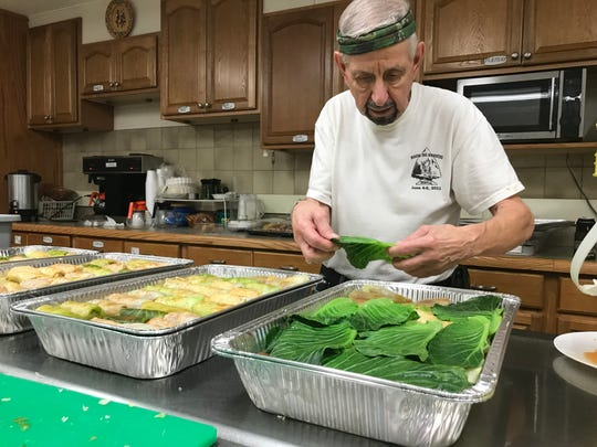 George Husnay, of Binghamton, tops uncooked holupki with cabbage leaves on July 17, 2019 in anticipation for St. Cyril's Parish Festival.