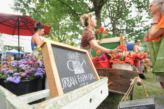 Wallis Carney gathers a bouquet of flowers at the Black Mountain Tailgate Market on July 13. Urban Farm Girl, which is owned by Bryan and Elaine Young, is one of two dozen members of the market.