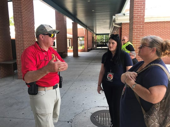 Rockledge Police Officer Jay Seyferth talks with Khursten Hofstetter and Kelly Caceres about role playing as victims during active shooter training for the Rockledge Public Safety Department.