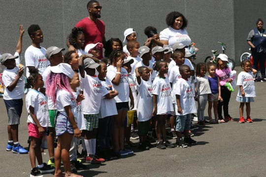 Former NBA standout Jason Thompson (rear red shirt) takes a picture at a bike giveaway his foundation sponsored in June at the Walmart in Mount Laurel on Route 73. Less fortunate children were given bicycles with the hope being that they exercise rather than play video games often.