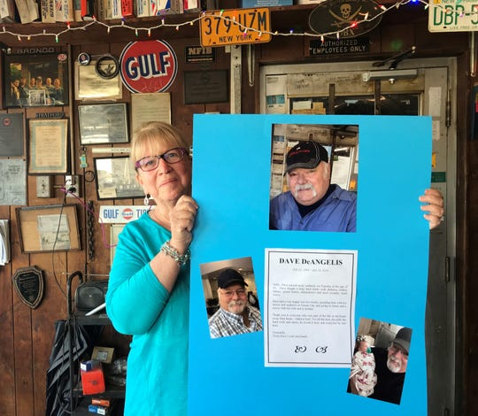Floss DeAngelis holds a memorial poster for her late husband, Dave DeAngelis Jr., at Oaklyn Gulf Service on Wednesday.