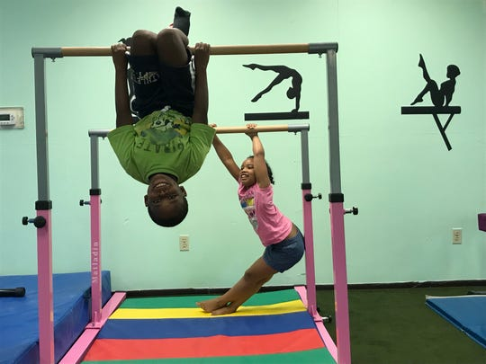 Naeem Paige, 9, hangs from the uneven bars while Victoria Perez, 7, holds on behind him. The two attend summer camp and participate in gymnastics at DARE Academy and DARE 2 Flip.