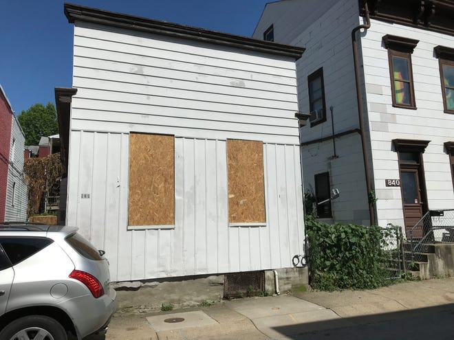 JULY 17 2019: Boards cover the front windows that were damaged by gunshots July 9 at house on Perry Street in Covington, a narrow street one block in length accessible off a one-way street. Police are investigating if a woman inside the home near the windows when the shots were fired was targeted or not.