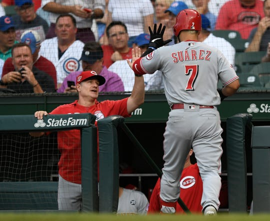 Cincinnati Reds' Eugenio Suarez (7) celebrates with manager David Bell, left, at the dugout after hitting a solo home run during the first inning of the team's baseball game against the Chicago Cubs on Tuesday, July 16, 2019, in Chicago.