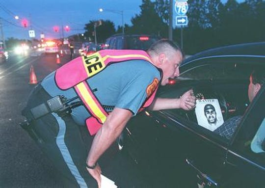 In this 2000 photo Officer Daniel Snyder of the Bernards Township Police Department shows a motorist a composite sketch of the shooting suspect during a checkpoint on King George Road. An anonymous donor has put up $5,000 for information leading to the arrest and conviction of the killer.