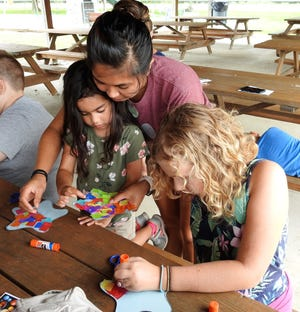 Rose Hall helps her daughter, Ramona Hall, 4, with a star craft next to Clara Young, 9. The Coshocton Public Library System has been having space activities as part of the summer reading program this summer tying into the 50th anniversary of the moon landing.