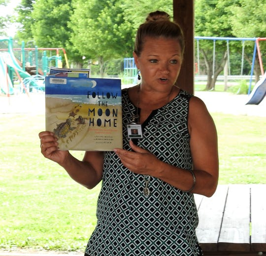 "Cyndi Shutt, children's librarian with the Coshocton Public Library, shows the book ""Follow the Moon Home"" by Deborah Hopkinson and Philippe Cousteau Jr. to kids at a recent program at the shelter outside Conesville Elementary School."