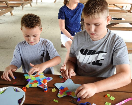 "Carrick Young, 6, and Charlie Young 11, work on a star craft relating to the book ""Draw Me a Star"" by Eric Carle during a recent program at the shelter outside Conesville Elementary School part of the Coshocton Public Library's ""A Universe of Stories"" summer reading program."