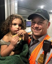 Lt. Brandon Kieft with the Michigan Department of Natural Resources holds Gabriella Vitale in the search and rescue command center while waiting for her family to arrive. Vitale was missing for more than 24 hours in northern Michigan.