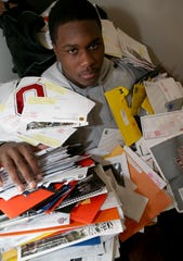 Defensive lineman for the Southfield football team Malik McDowell with some of the thousands of recruiting letters from colleges all over the country Wednesday, January 29, 2014.