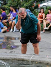 Russ Wilson splashes water on his face from a fountain in New York, Wednesday, July 17, 2019. The heat wave that has been roasting much of the U.S. in recent days is just getting warmed up, with temperatures expected to soar to dangerous levels through the weekend.