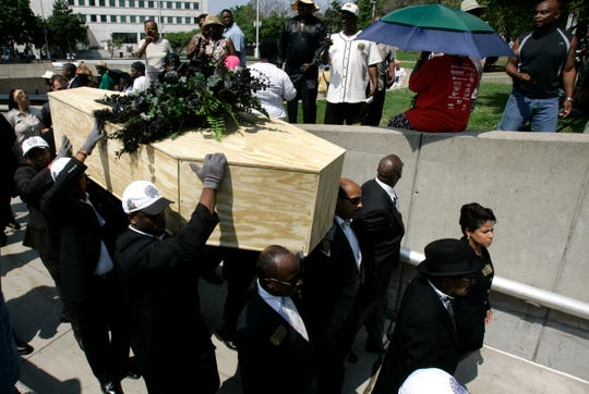 In a ceremony similar to one six decades ago, the NAACP is putting to rest a long-standing symbol of racism by holding a public burial for the N-word during its annual convention in Detroit, Monday, July 9, 2007. National Association for the Advancement of Colored People delegates from across the country gathered Monday and marched about a quarter-mile to Hart Plaza for a ceremony and rally.  Along the way, two Percheron horses pulled a pine box on top of which sat a bouquet of fake black roses. The N-word has been used as a slur against blacks for more than a century. (AP Photo/Carlos Osorio)