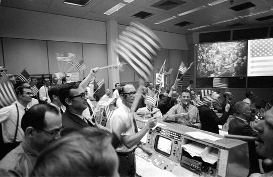 Flight controllers at the Mission Operations Control Room in the Mission Control Center at the Manned Spacecraft Center in Houston, celebrate the successful conclusion of the Apollo 11 lunar landing mission on July 24, 1969.