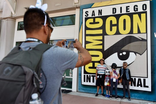 Luis Ramos, left, of San Diego takes a picture of his son Alek, third from right, and daughter Anabel, second from right, and their friends Emiliano Beltran, fourth from right, and Isabel Beltran,  before Preview Night at Comic-Con International at the San Diego Convention Center, in San Diego. T