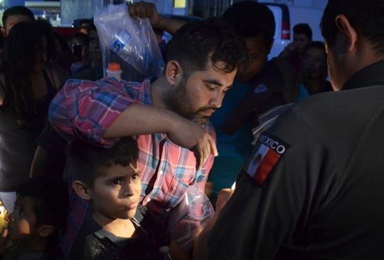 Migrants have their names checked by immigration officials as they board a bus that will take them to the city of Monterrey at an immigration center on the International Bridge 1, in Nuevo Laredo, Mexico, Tuesday, July 16, 2019.