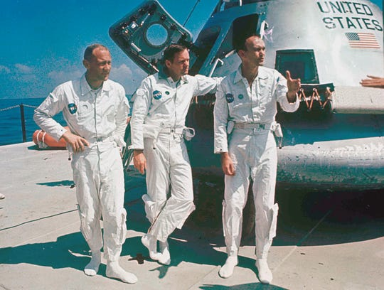 Apollo 11 astronauts stand next to their spacecraft in 1969, from left:  Col. Edwin E. Aldrin, lunar module pilot; Neil Armstrong, flight commander; and Lt. Michael Collins, command module pilot.