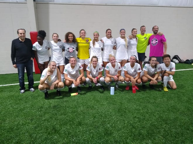 Members of the Motor City FC celebrate after winning Michigan Milk Cup on Tuesday. The team defeated the Detroit Sun 7-0.
