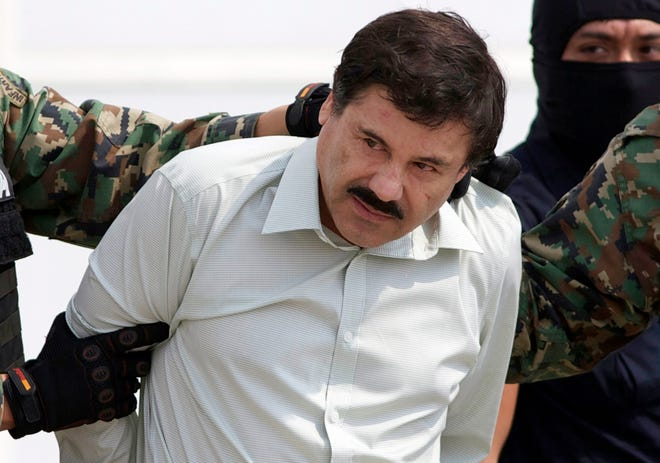 """Joaquin """"El Chapo"""" Guzman, the head of Mexico's Sinaloa Cartel, is escorted to a helicopter in Mexico City in 2014. Federal prosecutors want to recover $12.6 billion in drug money they say was generated by the Mexican drug lord."""