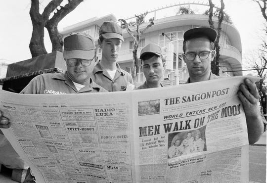 American servicemen pause on a downtown Saigon, Vietnam street to read a local newspaper account of the Apollo 11 lunar landing, July 21, 1969.