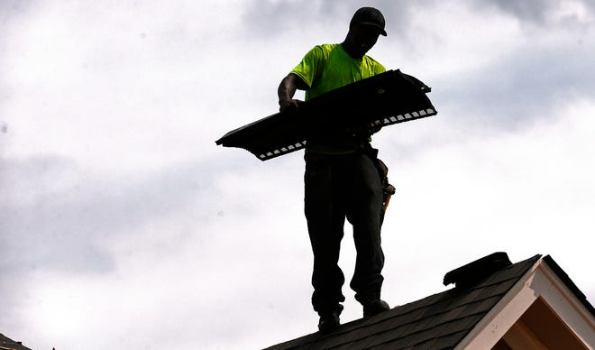 Larry McGee balances along a roof edge as he carries roof over ridge vent that he and others will be laying down on a new house in a Brandon, Miss., neighborhood.