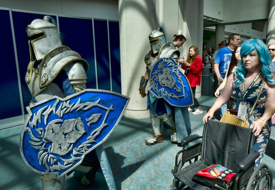 "Attendees Michael Mijerark, left, and Ryan Trent, center, dress as knights from ""Warcraft,"" at Comic-Con International in San Diego."