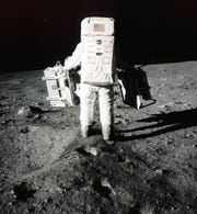 "Edwin ""Buzz"" Aldrin carries equipment for  scientific experiments to a deployment site south of the lunar module Eagle on July 20, 1969."