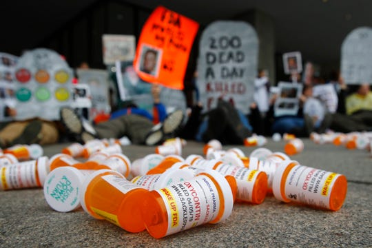Containers depicting OxyContin prescription pill bottles lie on the ground in front of the Department of Health and Human Services' headquarters in Washington as protesters demonstrate against the FDA's opioid prescription drug approval practices.