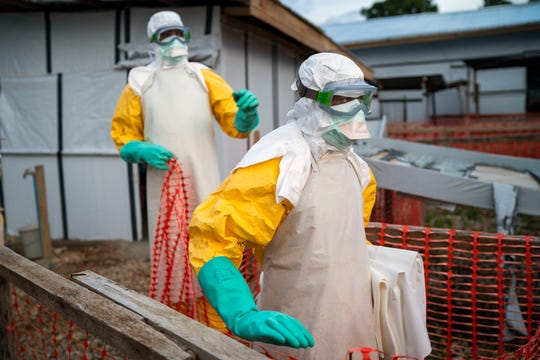 Health workers wearing protective suits take their shift at a treatment center in Beni, Congo DRC.
