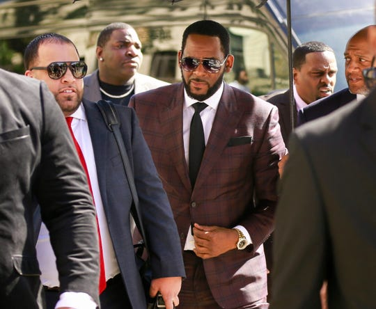 R&B singer R. Kelly, center, arrives at the Leighton Criminal Court building for an arraignment on sex-related felonies in Chicago o  June 26, 2019.