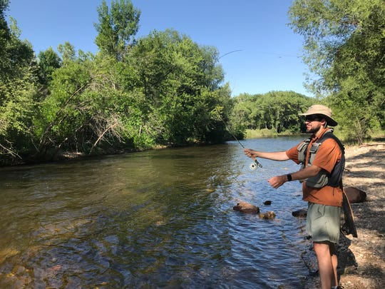 Ryan Collins of Durham, North Carolina, does a Michael Jordan impression with tongue out while fly fishing the Poudre River along the Poudre River Trail near Lee Martinez Farm.