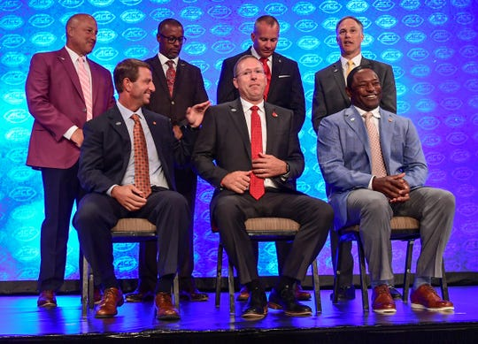 Clemson Head Coach Dabo Swinney, lower left, Louisville coach Scott Satterfield, middle, and Syracuse coach Dino Babers, right, get ready for a group photo with Boston College coach Steve Addazio, upper left, Florida State coach Willie Taggart, N.C. State coach Dave Doeren, and Wake Forest coach Dave Clawson, during ACC Media Football Kickoff at the Westin Charlotte Wednesday.