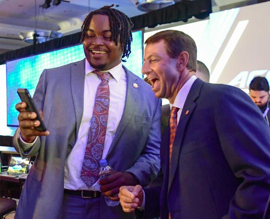 Clemson offensive guard John Simpson, left, shows Clemson Head Coach Dabo Swinney his phone during ACC Media Football Kickoff at the Westin Charlotte Wednesday.