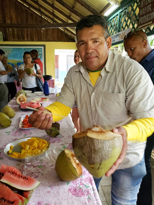 A Cuban farmer offers a coconut.