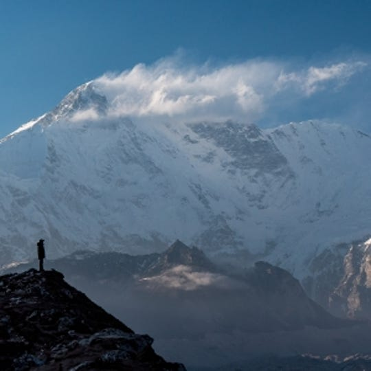While taking a break from coring high mountain lakes in the upper Gokyo Valley of Nepal, Montana State University Earth Sciences Ph.D. student Bibek Giri stands on the lateral moraine of the Ngozumba glacier with the peak of Cho Oyu (26,864') in the background.