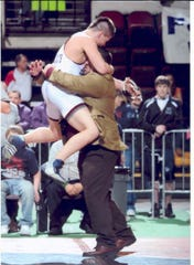 Harlem's Trent Jones, left, jumps into the arms of his coach, Lyle Faulkinberry, after winning his second straight state Class BC title at 171 pounds in 2011. at the All Class Tourney in Billings.