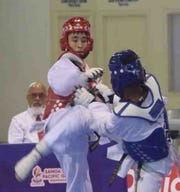 Leon Ho kicks his opponent in a match July 17 at the Pacific Games in Samoa.