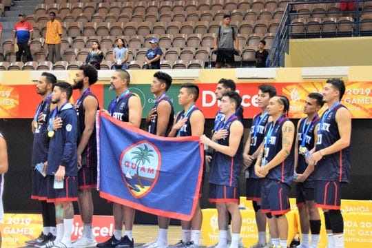 Players listen to the Guam national anthem after winning the gold medal at the XVI Pacific Games in Samoa July 17 with a convincing 83-74 victory over a tough Tahiti team.
