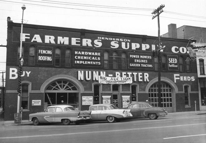 Henderson Farmers Supply Co. was located at 119-123 N. Elm St. and is now  parking lot. The business apparently opened in 1945 (it is not listed in the 1944 city directory and another photo of it is dated 1945) and lasted through about 1956. That's the model year of the newest car in this photo. Note the signs on the front of the building, one saying it was available for rent or lease, and the other advertising a big auction of merchandise, which may indicate it was going out of business in 1956.