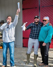 Henderson auctioneer Kevin Herron, left, solicits bids while country music star Luke Bryan (center) and legendary TV fishing show host Bill Dance look on during the fundraising auction at the Red Bird Games in Franklin, Tenn., last fall. Bryan and his wife, Caroline, organized the private event to raise awareness and funds for the Brett Boyer Foundation.