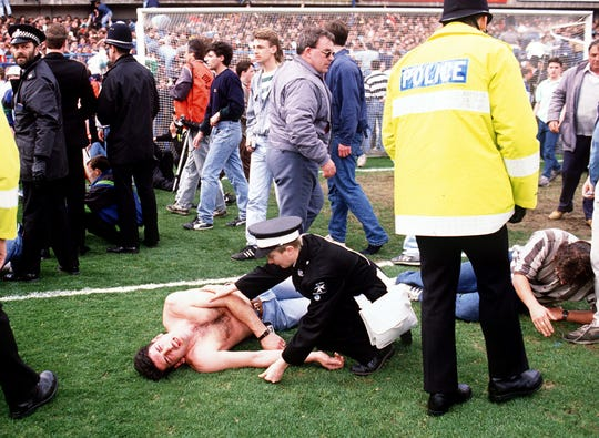 Policemen rescue soccer fans at Hillsborough stadium 15 April 1989 when 96 fans were crushed to death and hundreds injured after support railings collapsed during a match between Liverpool and Nottingham Forest.