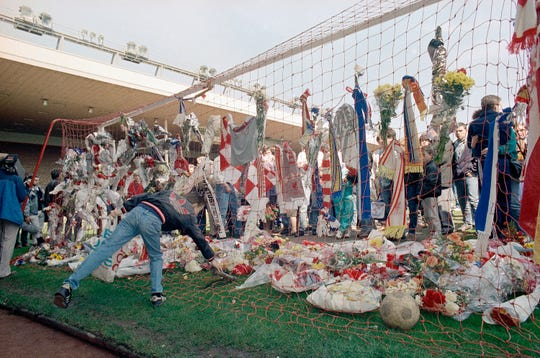 FiLE - In this file photo dated April 16, 1989, a Liverpool Football Club fan places a pair of football boots in the goal at the Kop end of Anfield Stadium as hundreds came to mourn the loss of fellow Liverpool fans.  The Hillsborough disaster was a fatal human crush during an English FA Cup semi-final soccer match between Liverpool and Nottingham Forest at Hillsborough Stadium on 15 April 1989, where 96 people died and many hundreds injured.