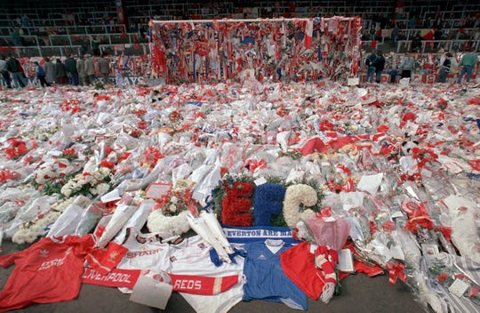 FILE - Liverpool soccer fans arrive at Anfield Stadium to pay their respects as flower tributes cover the 'Kop' end of the field, in Liverpool, on April 17, 1989, following April 15, when fans surged forward during the FA Cup semi-final between Liverpool and Nottingham Forest at Hillsborough Stadium in Sheffield, when the crash barriers gave way, killing 96 Liverpool fans and injuring over 200 others.